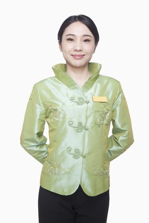 usher: RestaurantHotel Hostess in Traditional Chinese Clothing, Hands Behind Back Stock Photo