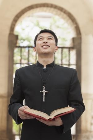 Young Priest Looking to Sky in Front of Doorway Stock Photo