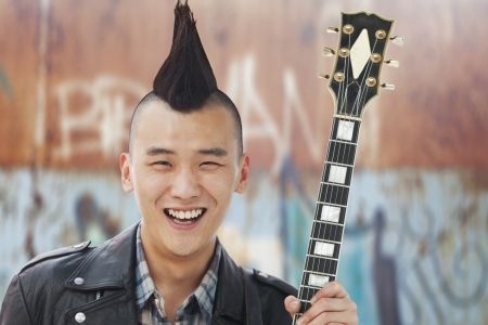 mohawk: Young man with punk Mohawk holding guitar Stock Photo