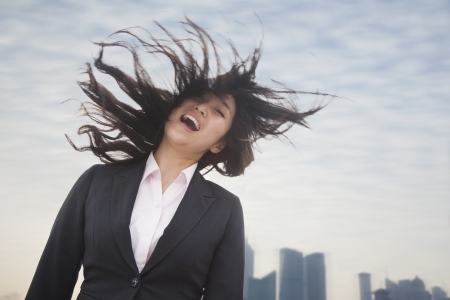 Young businesswoman smiling with hair blowing photo