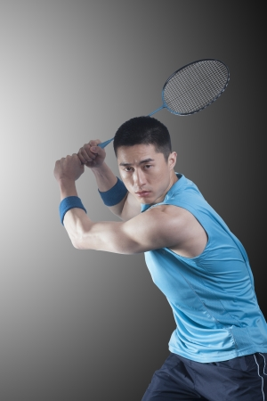 badminton racket: Young man playing badminton, racket raised Stock Photo