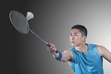 badminton racket: Young man playing badminton, hitting