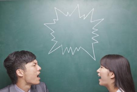 Zwei junge Leute schreien einander an vor der Tafel Standard-Bild - 35987435