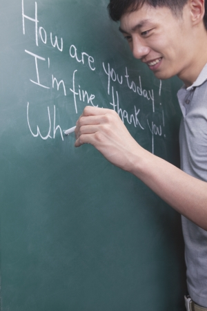 writing western:  Young man writing English sentences on the blackboard