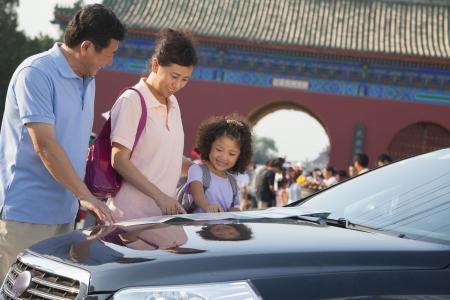 Abuelos y nieta de pie junto al coche y mirando el mapa