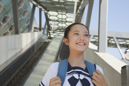 subway station: Girl standing and smiling next to the escalator near the subway station Stock Photo