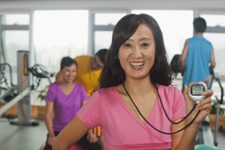 Woman holding stopwatch on foreground, people working out in the gym on the background photo
