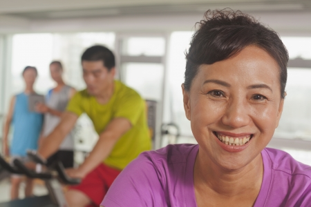 Woman smiling and exercising on the exercise bike photo