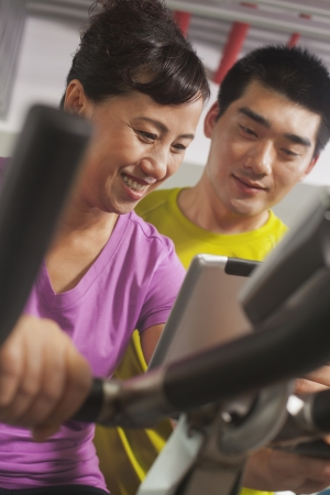 Woman smiling and exercising on the exercise bike with her trainer photo