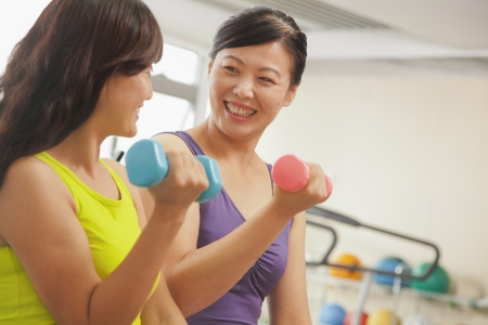mature women: Two mature women lifting weights in the gym Stock Photo