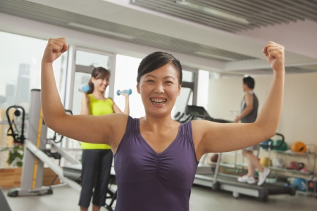 mature women: Mature women showing her strength after workout in the gym Stock Photo