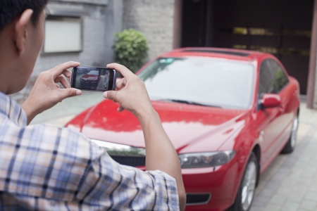 Young Man Taking a Picture of His Car