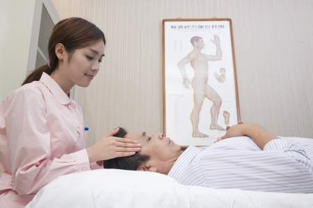 masseuse: Masseuse Giving Chinese Traditional Medical Facial Massage