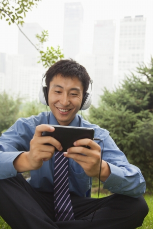 legs crossed at knee: Young businessman listening to music on his MP4 player Stock Photo