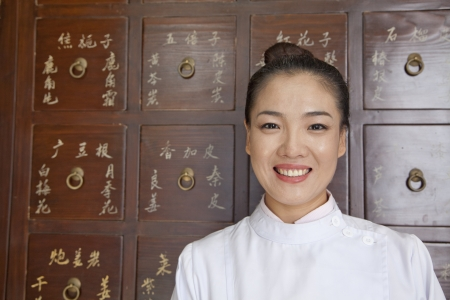 traditional culture: Portrait of Doctor In Front of Traditional Chinese Medicine Cabinet