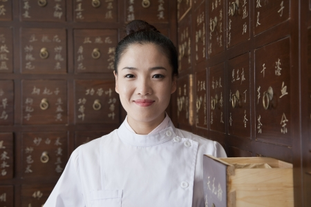 Portrait of Doctor In Front of Traditional Chinese Medicine Cabinet