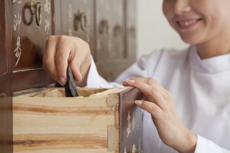 medicina tradicional china: El doctor Taking hierba usada para la Medicina Tradicional China de un cajón