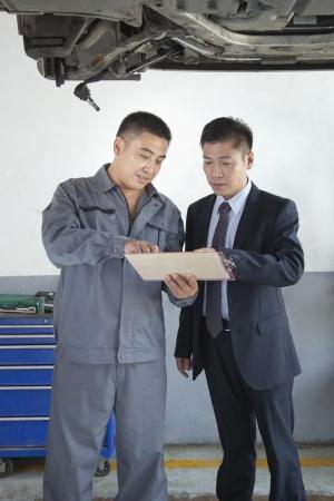 explaining: Mechanic Explaining to Businessman