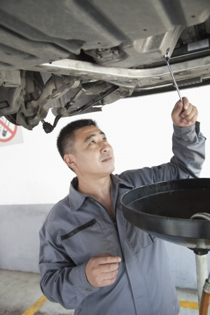 shop skill: Mechanic Changing the Oil Stock Photo