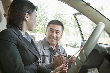 Mechanic Explaining to Businesswoman