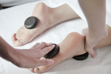 Woman Receiving Hot Stone Foot Massage Stock Photo