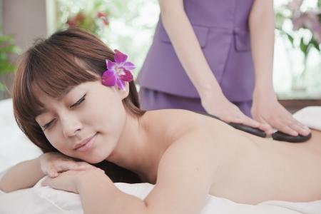 Woman Receiving Hot Stone Massage photo