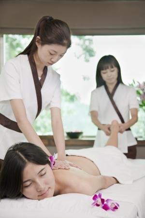 Two Masseuses Massaging One Woman photo