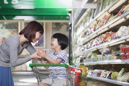 Mother and daughter holding apple, shopping for groceries, Beijing photo
