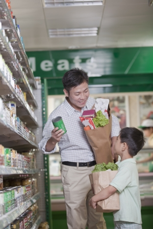 western script: Father and son shopping together in supermarket, Beijing Stock Photo