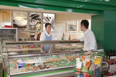 sales clerk: Sales Clerk assisting man at the Deli counter, Beijing Stock Photo