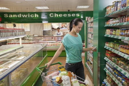 Woman looking at shopping list in supermarket, Beijing photo