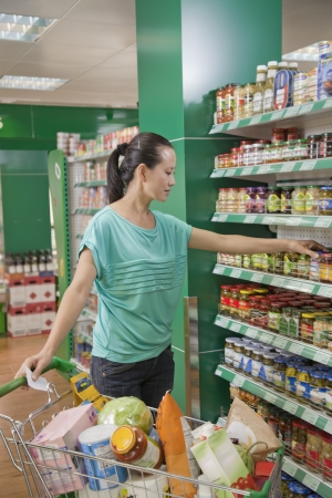 Woman reaching for jar on the shelf in the supermarket, Beijing photo