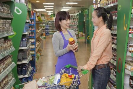 Sales clerk assisting women, holding jar in the supermarket, Beijing