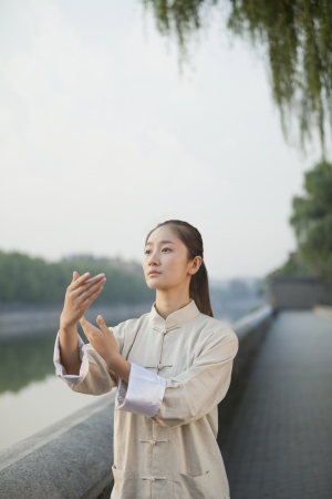 Young Woman Practicing Tai Ji Stock Photo