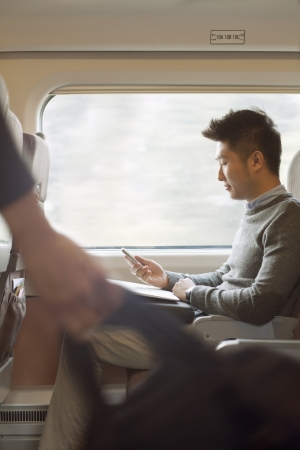 trains: Young man sitting on a train using his phone Stock Photo