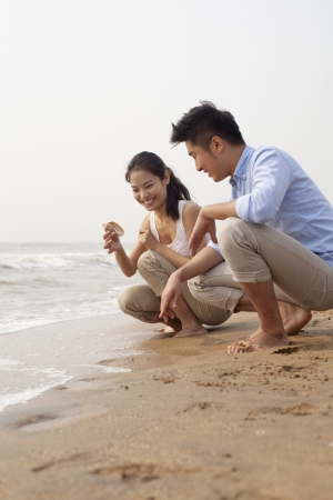 water's edge: Young couple looking at seashell at the waters edge, China
