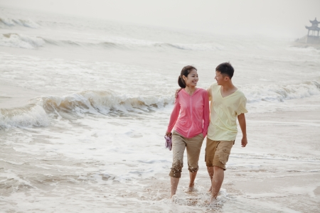 water's edge: Young couple walking by the waters edge on the beach, China