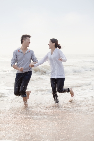 waters  edge: Young couple holding hands and running by the waters edge on the beach, China