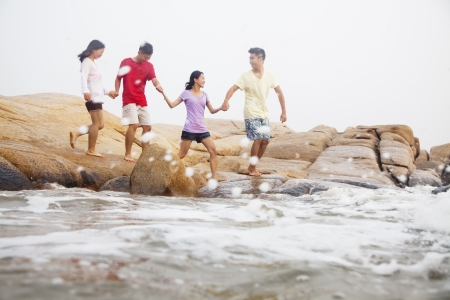 Four friends walking over rocks by the sea photo