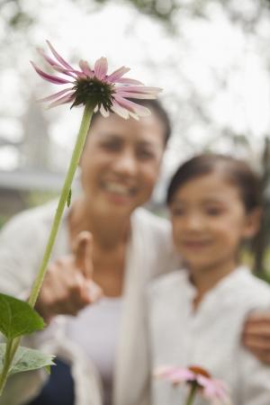 祖母と孫娘の庭で花を見て