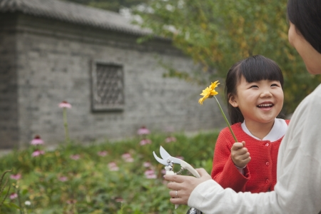 Smiling young girl with flower photo