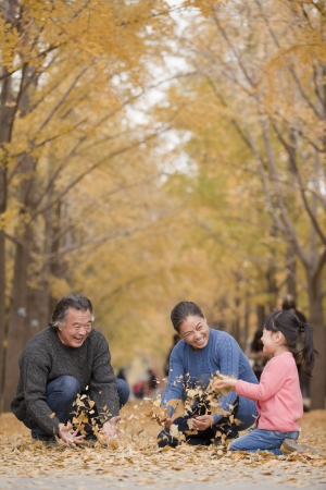 Grandparents and granddaughter playing in park photo