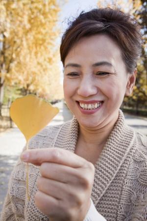ginkgo leaf: Mature Woman Holding Yellow Ginkgo Leaf