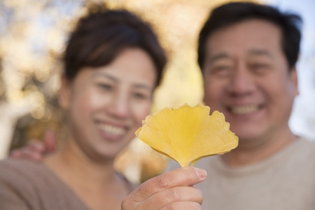 Mature Couple Looking at the Leaf in the Park photo