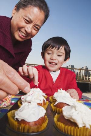 familia pic nic: Abuela y nieto decorar bizcochos