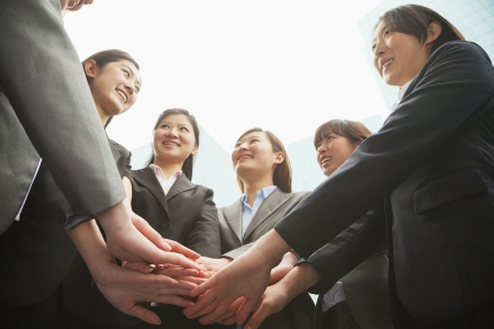 medium body: Group of young businesswoman putting hands together in a circle