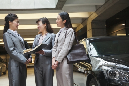 parking garage: Three young businesswomen meeting and talking in parking garage
