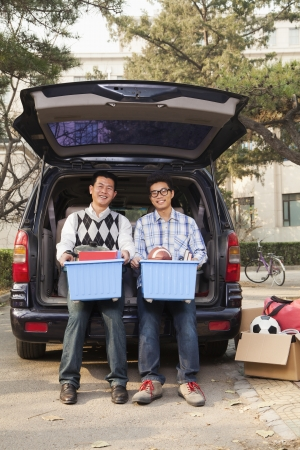 Father and son unpacking car for college photo
