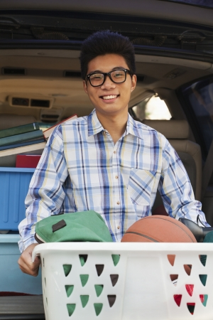 dorm: Portrait of boy with college dorm items in back of car
