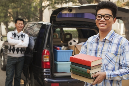 family moving house: Boy unpacking car for college Stock Photo